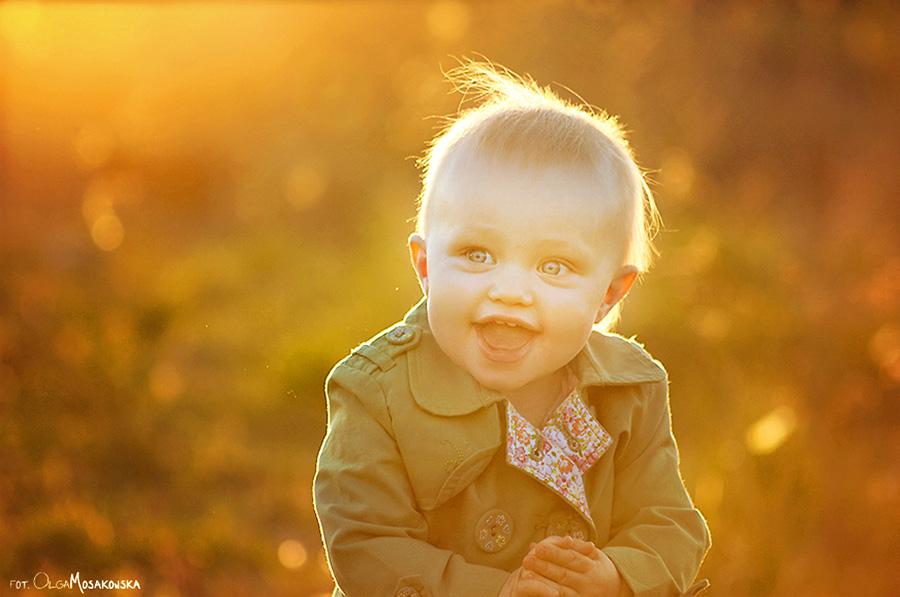 Plenerowa sesja dziecięca. Zdjęcie dziewczynki zrobione pod słońce.