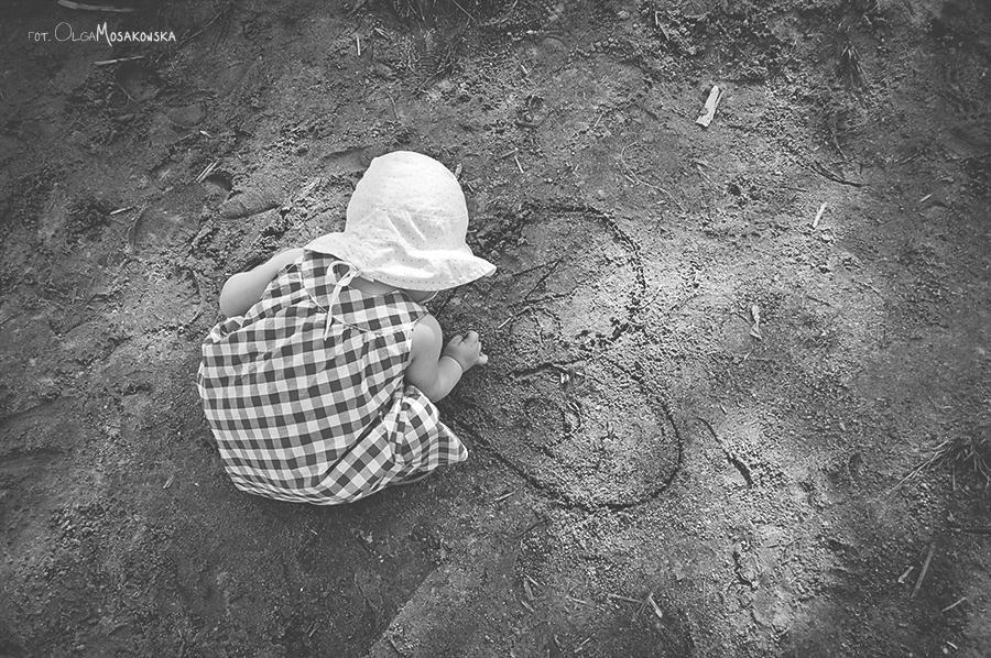Czarno-biała fotografia dziecka rysującego po piasku.