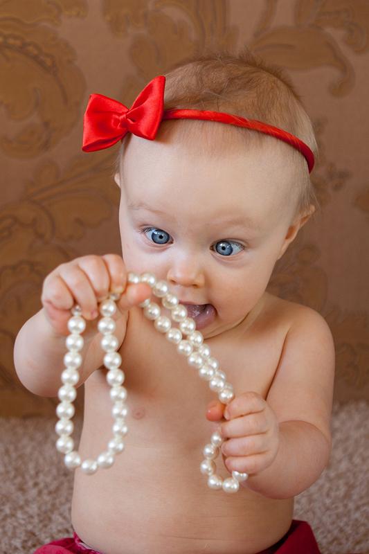 Zdjęcie małej dziewczynki ze śmieszną miną - w opasce i koralach.