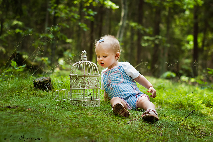 Zdjęcie dziecka siedzącego w lesie. Fotograf dziecięcy Olsztyn.