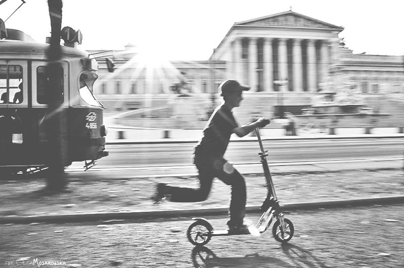 Czarno-biała fotografia chłopca jadącego na hulajnodze w Wiedniu. Kinderfotografin Wien.