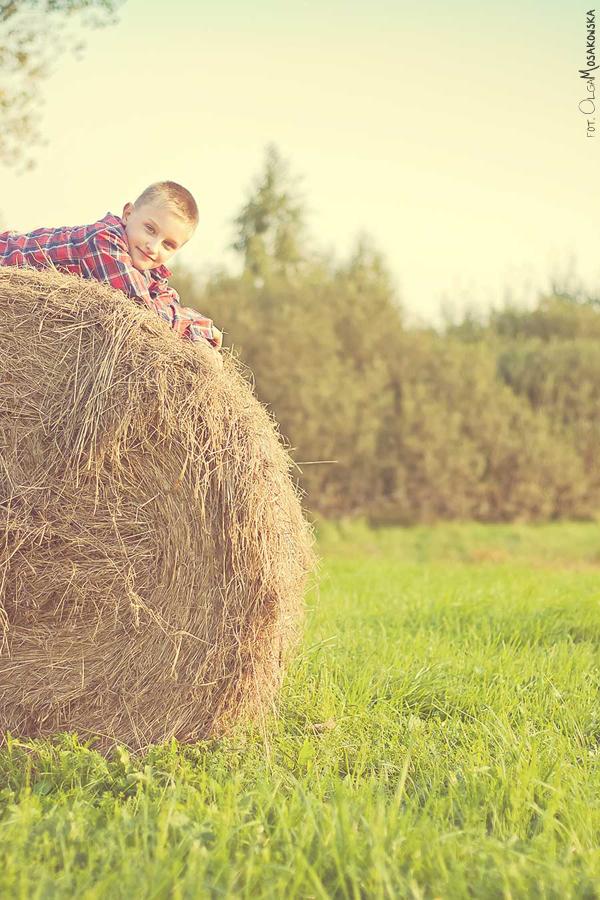 Sesja zdjęciowa dziecka w plenerze, na sianie. Fotograf Olsztyn.