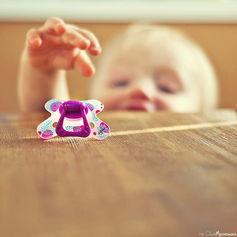 Zdjęcie dziecka sięgającego po smoczek.