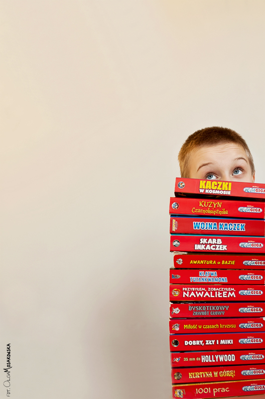 Projekt fotograficzny - dziecko i jego ulubionych 13 rzeczy. Portret starszego dziecka, chłopca ze stertą książek.