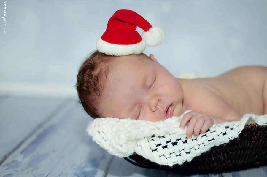 śpiący noworodek ze świąteczną czapką na głowie, podczas sesji zdjęciowej.